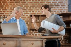 Young man holding blueprint and high-fiving his mentor. Well done. Cheerful young men holding a big blueprint in his hand and giving a high five to his senior royalty free stock photos