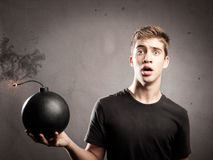 Young man holding a bomb. Scared young man holding an old-fashioned bomb Royalty Free Stock Photos