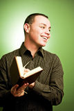 Young man holding book. A studio view of a smiling young Hispanic man holding an open hardcover book.  Green background Royalty Free Stock Images