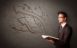 Young man holding book with arrows Royalty Free Stock Photo