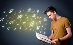 Young man holding book with letters Royalty Free Stock Images