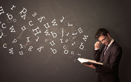 Young man holding book with letters Stock Photos