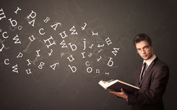 Young man holding book with letters Stock Images