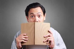 Young Man Holding Book, Mouth Covered by Book royalty free stock photography