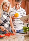 Young Man Holding Book Next to Woman Cooking Royalty Free Stock Images