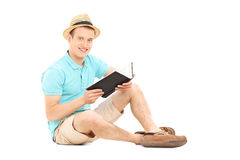 Young man holding a book seated on floor Royalty Free Stock Photography