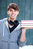 Young man holding books outside with headphones Stock Photo
