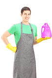 Young man holding a bottle of cleaning liquid Stock Photos