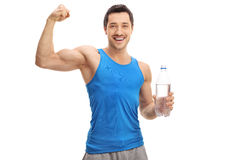 Young man holding bottle of water and flexing his biceps Royalty Free Stock Photography