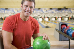 Young man holding a bowling ball in a bowling alle. Portrait of a young man holding a bowling ball in a bowling ally smiling Royalty Free Stock Images