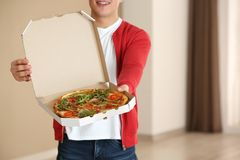 Young man holding box with tasty pizza indoors stock image