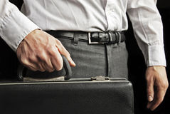 Young man holding a briefcase. Studio shot of young caucasian man holding a briefcase Royalty Free Stock Image