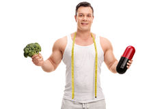 Young man holding broccoli and a diet pill Stock Photography