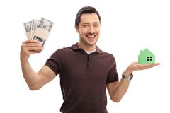Young man holding bundles of money and a model house. Isolated on white background Stock Photos
