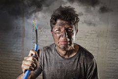 Young man holding cable smoking after electrical accident with dirty burnt face in funny sad expression Stock Photos
