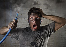Young man holding cable smoking after electrical accident with dirty burnt face in funny sad expression. Young man holding electrical cable smoking after Royalty Free Stock Photography