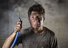 Young man holding  cable smoking after electrical accident with dirty burnt face in funny sad expression Royalty Free Stock Photos