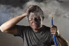 Young man holding cable smoking after electrical accident with dirty burnt face in funny sad expression Stock Image