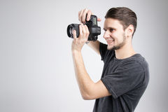 Young man holding camera in black shirt isolated studio Stock Photo