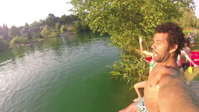 Young man holding camera while jumping into river with friends stock video