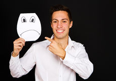 Young man holding card with a angry face Royalty Free Stock Image