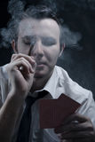 Young man holding cards and cigar in smoke Royalty Free Stock Photo