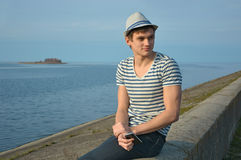 Young man holding a cell phone and smiling. Young man holding on a cell phone and smiling. The young man in the hat and striped t-shirt sitting on the parapet in royalty free stock image