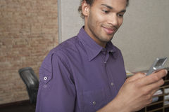 Young man Holding Cellphone In Office Stock Image
