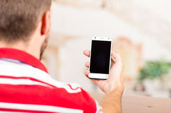 Young man holding cellphone Stock Image