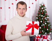 Young man holding christmas present box in decorated room Stock Photos