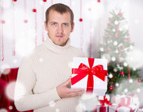 Young man holding christmas present box in decorated room Stock Photography