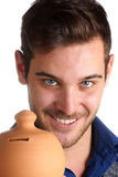 Young man holding a clay moneybox Royalty Free Stock Image
