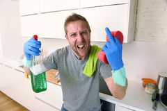 Young man holding cleaning detergent spray and sponge washing home kitchen clean angry in stress Royalty Free Stock Photo