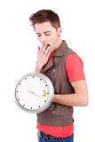 Young man holding a clock Stock Image