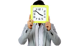 Young man holding clock covering his face Royalty Free Stock Image