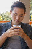 Young man holding coffee cup or hot tea Stock Photography