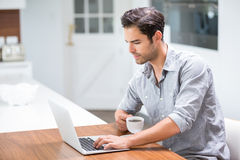 Young man holding coffee cup while working on laptop Stock Photography