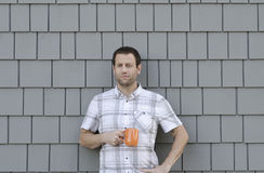 Young man holding a coffee mug with a grey neutral background. Royalty Free Stock Photography