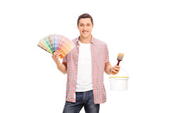 Young man holding color swatch and a paintbrush. Studio shot of a cheerful young man holding a color swatch and a paintbrush isolated on white background royalty free stock photography