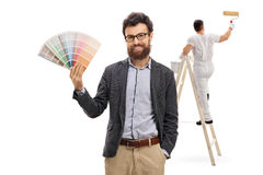 Young man holding color swatch with painter painting Stock Photos