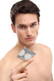 Young man holding condom Royalty Free Stock Photos