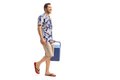 Young man holding a cooling box and walking. Full length profile shot of a young man holding a cooling box and walking isolated on white background stock photo