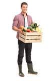 Young man holding a crate full of vegetables Royalty Free Stock Photo
