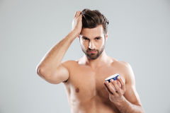 Young man holding cream isolated Stock Photos