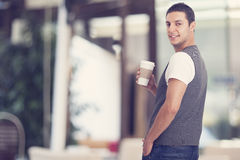 Young man holding a cup of coffee Stock Images