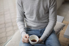 Young man holding cup of coffee  inside the coffee shop Royalty Free Stock Photos