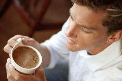Young man holding cup of coffee, side view, close-up, elevated view Royalty Free Stock Images