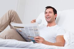 Young man holding cup in hand reading newspaper Royalty Free Stock Photography