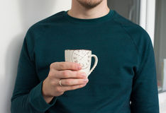 Young man holding a cup. Man drinks coffee or tea in the morning at work, home Stock Photo
