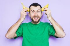 Young man holding cut in half banana on the level of temples. Young bearded man holding cut in half yellow banana on the level of temples, smiling and happy face royalty free stock photos